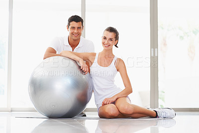 Buy stock photo Portrait of smiling young woman and trainer with fitness ball