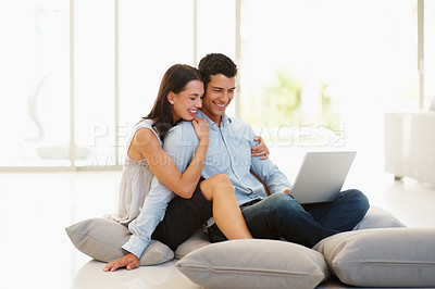 Buy stock photo Happy young couple using laptop at home