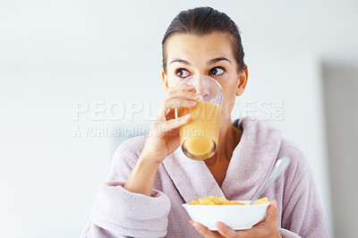 Buy stock photo Portrait of young woman drinking juice and holding bowl of fruits
