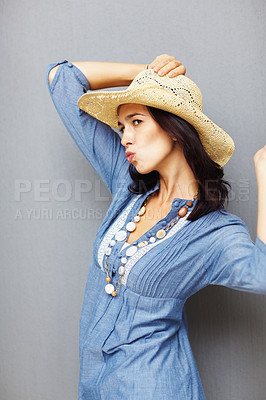 Buy stock photo Portrait of pretty young woman puckering while holding hat