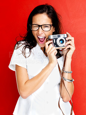 Buy stock photo Excited young woman in glasses winking with an old camera in hand against white background