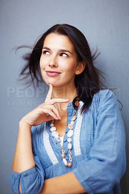 Buy stock photo Pretty young woman with finger on chin looking sideway