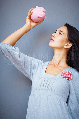 Buy stock photo Caucasian young female looking up into piggybank