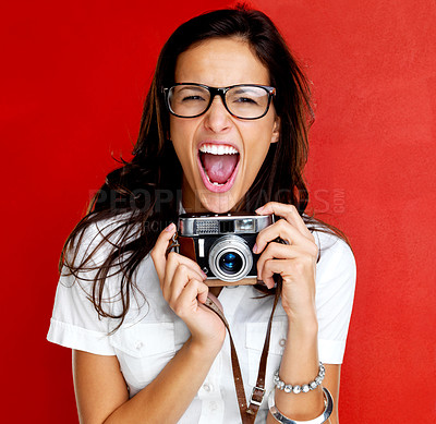 Buy stock photo An excited young woman photographer shouting and holding a vintage camera against a bright red background