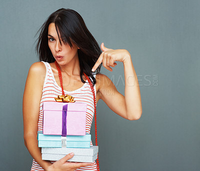 Buy stock photo Portrait of pretty young woman pointing at gifts against wall