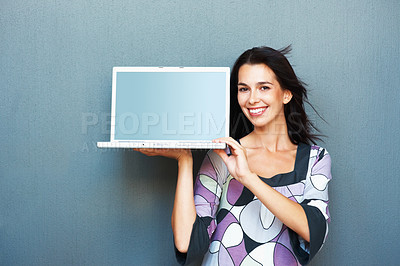 Buy stock photo Happy young woman displaying laptop against the wall