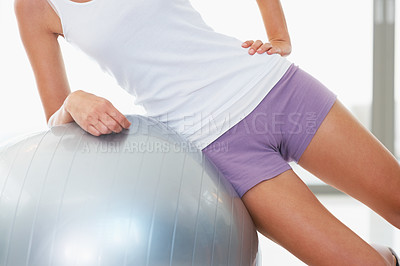 Buy stock photo Cropped image of woman doing side crunch exercise with fitness ball