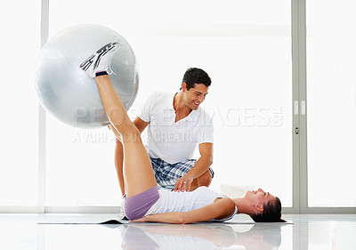 Buy stock photo Young woman exercising with fitness ball while trainer looking at her