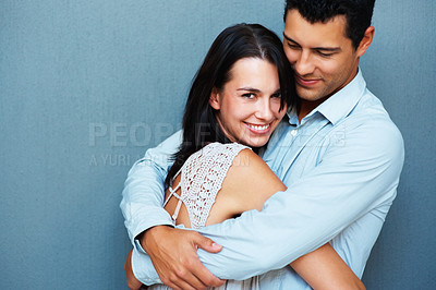 Buy stock photo Portrait of happy couple hugging each other on blue background