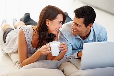 Buy stock photo Happy loving young couple with coffee cup and laptop
