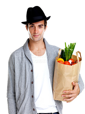 Buy stock photo Portrait of a handsome young man wearing a hat holding a grocery bag against white background
