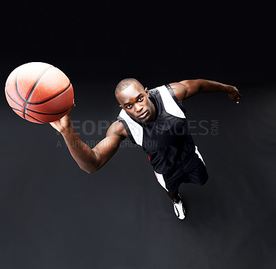 Buy stock photo Top view of a healthy young male basketball player practicing a hoop shot against black background
