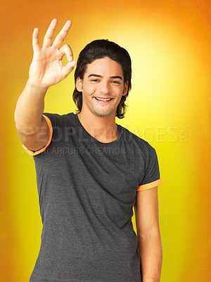 Buy stock photo Man standing against yellow background giving ok sign