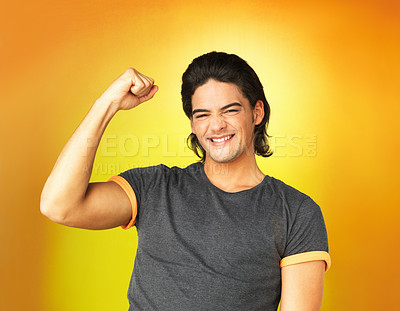 Buy stock photo Man standing against yellow background clenching fist