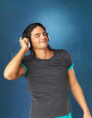 Buy stock photo Handsome man smiling with eyes closed while listening to headphones against a blue background
