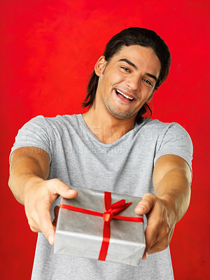 Buy stock photo Handsome latino man giving you a gift while smiling against a red background