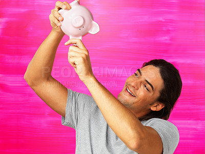 Buy stock photo Smiling man checking piggy bank