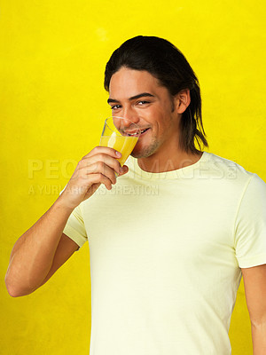 Buy stock photo Flirtatious man drinking juice against yellow background