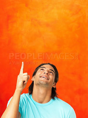 Buy stock photo Closeup of excited young man points up at copyspace