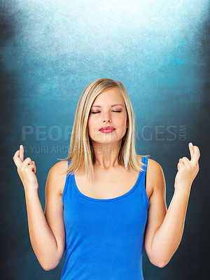 Buy stock photo Pretty woman crossing her fingers against blue background