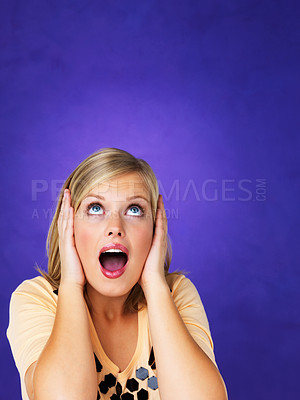 Buy stock photo Surprised young woman looking up at copyspace