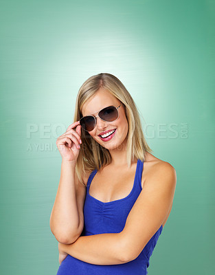 Buy stock photo Woman holding brim of glasses on green background