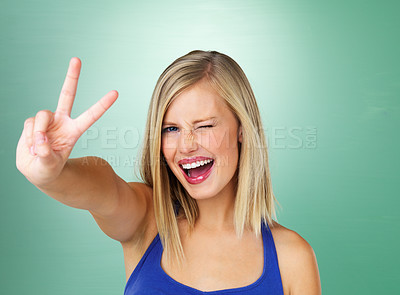 Buy stock photo Closeup of woman giving peace sign on green background