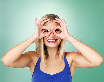 Buy stock photo Young woman looking through imaginary binoculars against a plain background