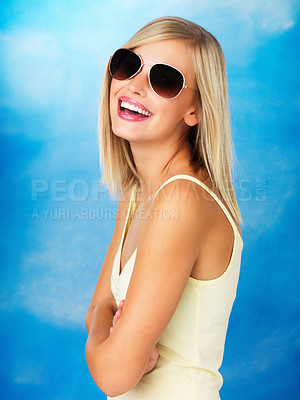 Buy stock photo Side view of happy woman with sunglasses on against blue background