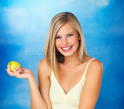 Buy stock photo Pretty woman holding apple against blue background