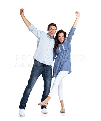 Buy stock photo Portrait of an attractive young couple celebrating success with hands raised over white background