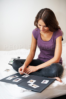 Buy stock photo Girl sitting on bed choosing photographs to go into a photo album