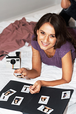 Buy stock photo Portrait of girl on bed putting together photo album