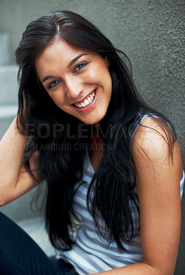 Buy stock photo Portrait of an attractive young woman sitting relaxed