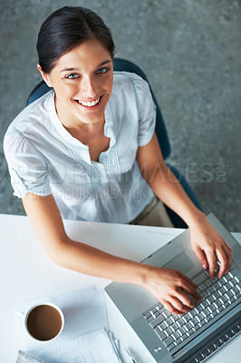 Buy stock photo Top view of a happy young female business executive working on laptop with a cup of coffee in the office