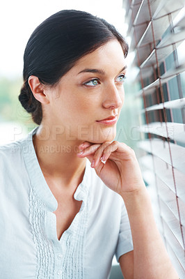 Buy stock photo Portrait of a cute young girl lost in deep thought while looking through window - indoor