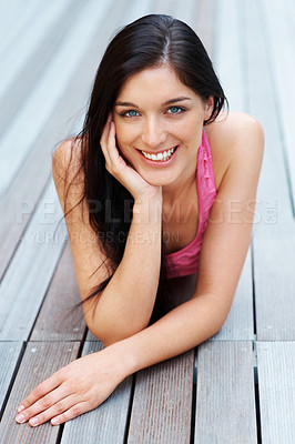 Buy stock photo Portrait of a happy young lady relaxing on the wooden floor