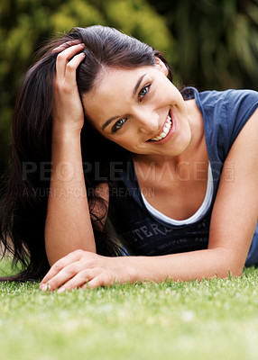 Buy stock photo Portrait of a charming young lady relaxing on grass in the park - Outdoor