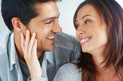 Buy stock photo Closeup portrait of a romantic young couple looking at each other