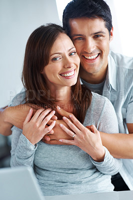 Buy stock photo Portrait of a handsome young man hugging his girlfriend and smiling
