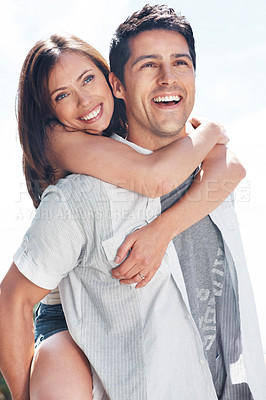 Buy stock photo Portrait of a smiling young couple enjoying piggyback ride - Outdoor