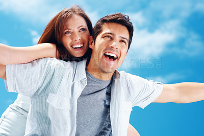 Buy stock photo Portrait of a smiling young man piggybacking his pretty girlfriend against the sky - Outdoor