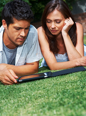 Buy stock photo Portrait of a lovely young couple using tablet while lying in the park - Outdoor