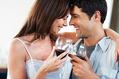 Buy stock photo Portrait of a romantic young couple toasting glasses of red wine and celebrating something