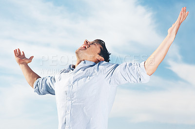 Buy stock photo Portrait of an excited young man celebrating his success against the sky - Outdoor
