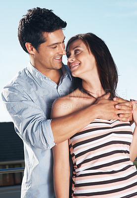 Buy stock photo Portrait of an affectionate young couple looking at each other- Outdoor