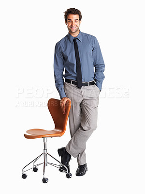 Buy stock photo Handsome executive casually standing near a chair
