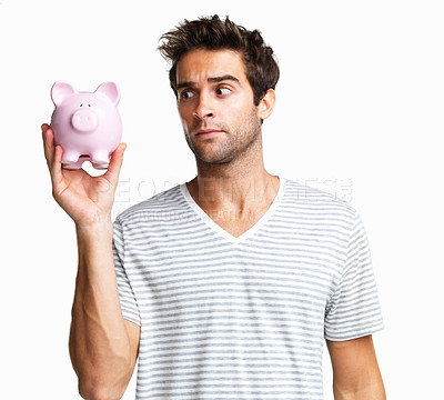 Buy stock photo Man holding up piggy bank looking uncertain