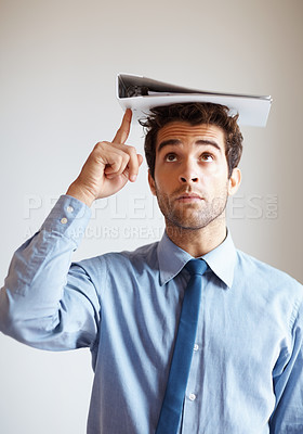 Buy stock photo Handsome executive pointing up at binder on head