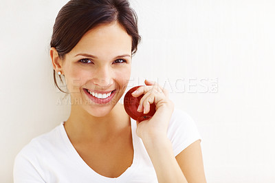Buy stock photo Portrait of happy young lady with a red apple smiling against white background